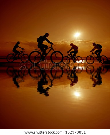 Image of sporty company four friends on bicycles outdoors against sunset. Silhouette A lot phases of motion of a single cyclist along the shoreline coast Reflection on water Space for inscription - stock photo