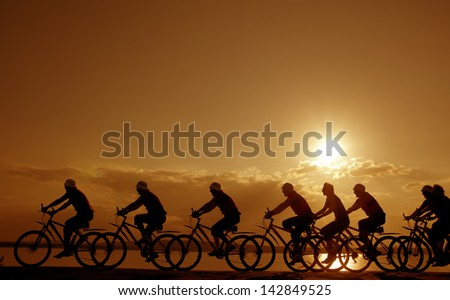 Image of sporty company friends on bicycles outdoors against sunset. Silhouette A lot phases of motion of a single cyclist along the shoreline coast - stock photo