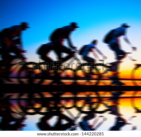 Image of sporty company friends on bicycles outdoors against sunset. Silhouette A lot phases of motion couple of cyclist along the shoreline coast With reflection on water - stock photo
