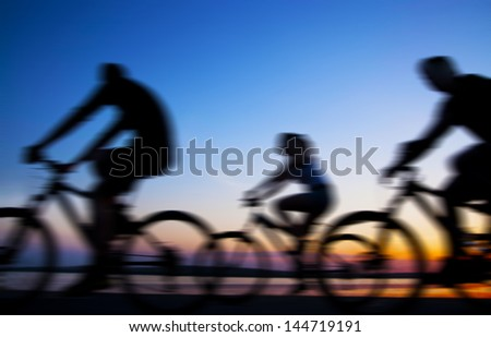 Image of sporty company friends on bicycles outdoors against sunset Silhouette . A lot phases of motion of a single cyclist along the shoreline coast copy Space for inscription - stock photo
