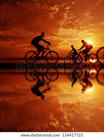 Image of sporty company friends on bicycles outdoors against sunset. Silhouette A lot phases of motion of a single cyclist along the shoreline coast Reflection on water Space for inscription - stock photo