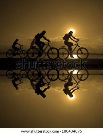 Image of sporty company friends on bicycles outdoors against sunset. Silhouette A lot phases of motion of four 4 cyclist along shoreline coast Reflection sun on water Copy Space for inscription - stock photo