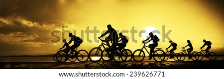 Image of sporty company friends on bicycles outdoors against sunset. Silhouette A lot phases of motion go of 8 eight cyclist along shoreline coast Reflection sun on water Copy Space for inscription - stock photo