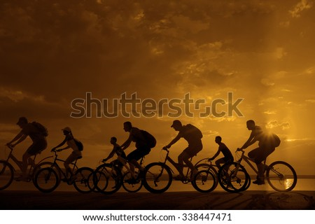 Image of sporty company friends on bicycles outdoors against sunset. Silhouette A lot phases of motion go of seven 7 cyclist along shoreline coast Reflection sun on water Copy Space for inscription - stock photo
