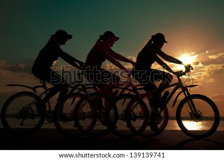 Image of sporty company friends on bicycles outdoors against sunset. Silhouette The three phases of motion of a single cyclist along the shoreline coast - stock photo