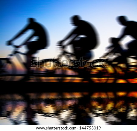 Image of sporty company friends on bicycles outdoors against sunset Silhouette with reflection on water . A lot phases of motion single cyclist along the shoreline coast copy Space for inscription - stock photo