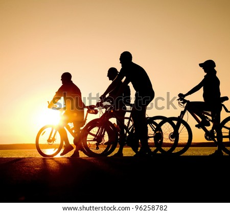 Image of sporty company teens on bicycles outdoors against sunset. Silhouette.