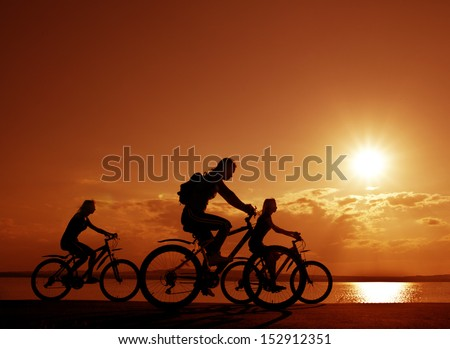 Image of sporty company three friends on bicycles outdoors against sunset. Silhouette A lot phases of motion of a single cyclist along the shoreline coast  Space for inscription - stock photo