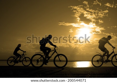 Image of sporty company three friends on bicycles outdoors against sunset. Silhouette motion of 3 cyclist along the shoreline coast and cloudy sunset sky background Space for inscription - stock photo