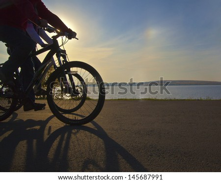Image of sporty couple on bicycles outdoors against sun and sunset. Silhouette with shadows No faces - stock photo