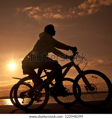 Image of sporty couple on bicycles outdoors against sunset. Silh - stock photo