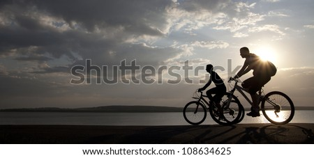 Image of sporty couple on bicycles outdoors against sunset. Silhouette.