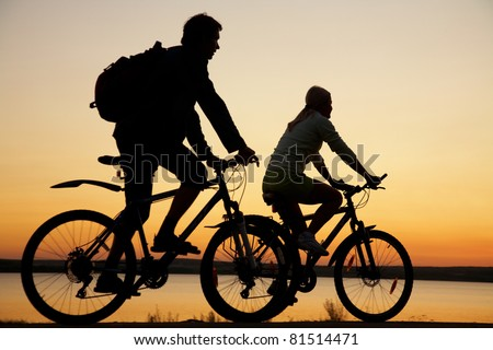 Image of sporty couple on bicycles outdoors against sunset. Silhouette. - stock photo