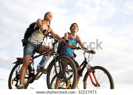 Image of sporty couple on bicycles outdoors looking somewhere with smiles - stock photo