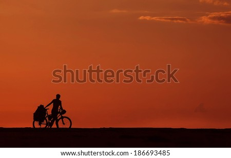 Image of sporty tourist man walking along the shore with the bike and hiking backpacks against sunset among the clouds. Silhouette - stock photo