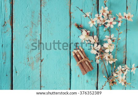 image of spring white cherry blossoms tree next to wooden colorful pencils on blue wooden table. vintage filtered image  - stock photo