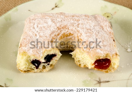Image of square donut with bite taken out in ceramic dish on brown sack background