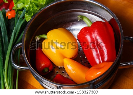 Image of steamer filled with washed peppers - stock photo