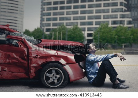 Image of stressful man sitting in front of a broken car after traffic accident on the road - stock photo