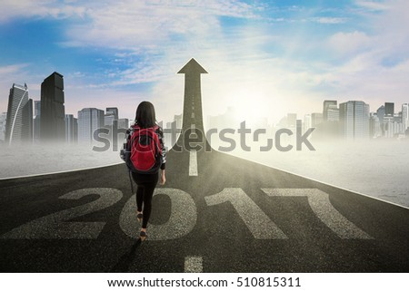 Image of student walking on the street with number 2017 toward upward arrow, symbolizing of better education for the future