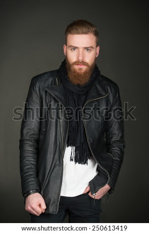 Image of stylish casual modern man with beard wearing leather jacket and looking at camera