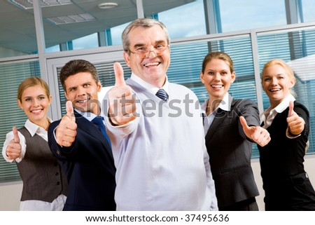 Image of successful business team keeping their thumbs up with senior leader in front smiling at camera - stock photo