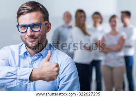 Image of successful businessman showing thumb up