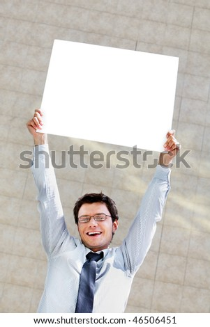 Image of successful male raising blank paper and looking at camera with smile