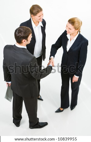 Image of successful partners shaking hands in the white room - stock photo