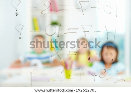 Image of sums written on transparent board with schoolmates on background - stock photo