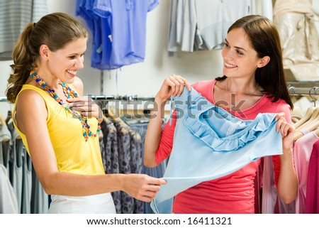 Image of surprised girl looking at blue tanktop in her friendâ??s hands in the department store - stock photo