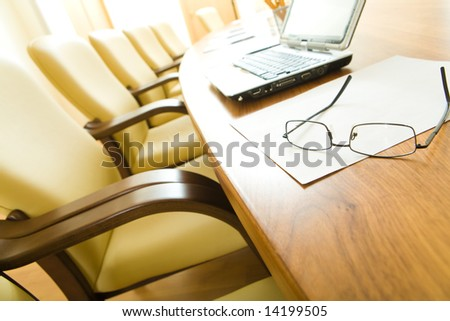 Image of table with laptop, papers, glasses on it with chairs near by in row - stock photo