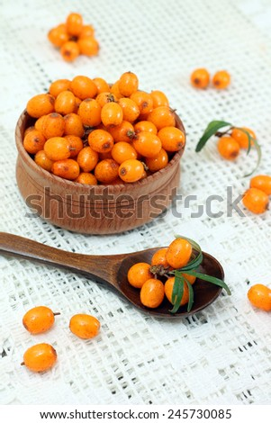 Image of tasty buckthorn in wooden bowl and spoon - stock photo