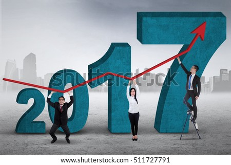 Image of teamwork is holding growth graph while standing in front of numbers  2017, shot outdoors