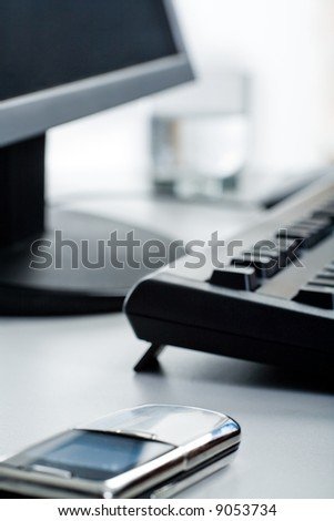 Image of telephone lying on a table with monitor, keyboard and glass on it - stock photo