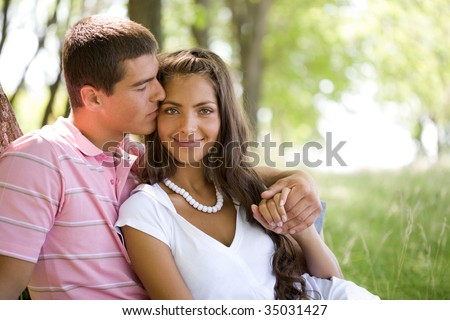 Image of tender man kissing girl?s face while she smiling at camera in natural environment - stock photo
