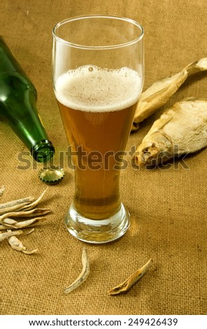 image of the bottle, a mug of beer and dry fish closeup
