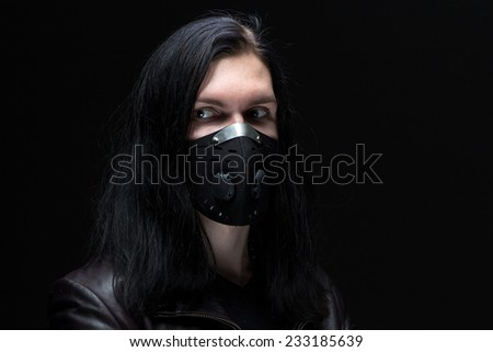 Image of the brunet man in mask on black background
