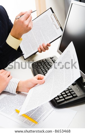Image of the business people's hands holding documents near computer