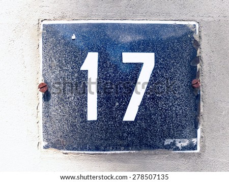 Image of the number 17 on a wall indicating a house number - stock photo