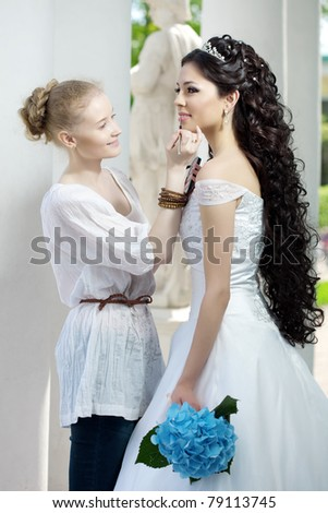 Image of the stylist takes care of the bride