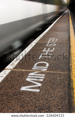 Image of the words, mind the step, painted as a safety warning on a train platform with a train passing. - stock photo