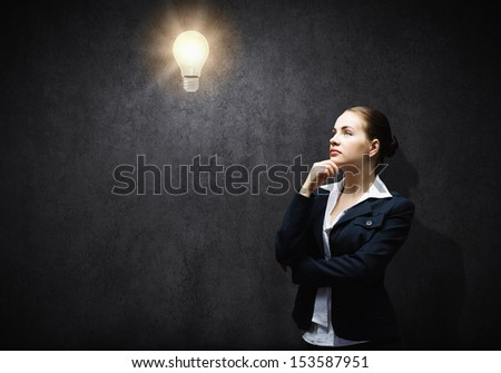 Image of thoughtful businesswoman looking at light bulb