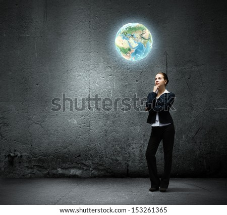 Image of thoughtful businesswoman looking at planet earth - stock photo