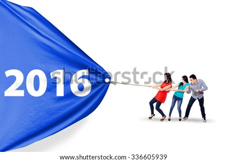 Image of three asian people work together to pull a big banner with numbers 2016, isolated on white background - stock photo