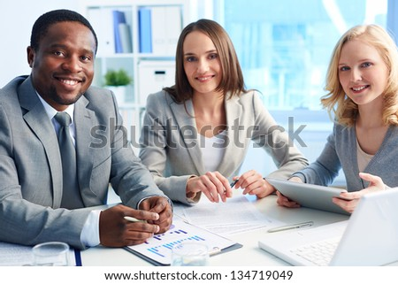 Image of three business partners looking at camera with smiles in office - stock photo
