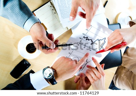 Image of three business people's hands pointing to the plan