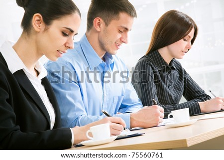 Image of three business people working at seminar
