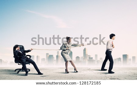 Image of three businesspeople pulling rope against city background - stock photo