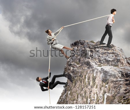 Image of three businesspeople pulling rope atop of mountain - stock photo